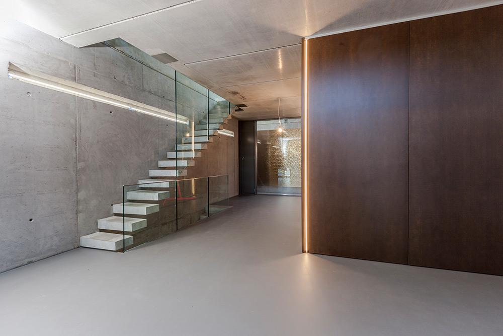 Freischwebende Treppe, dunkle Massivholzbohlen, puristisches Stahlgeländer, Zwinz